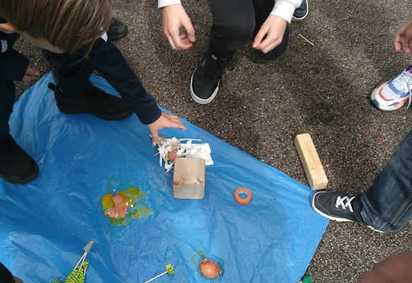 Students experimenting above a large blue plastic bag their egg-protectors from a falling brick.